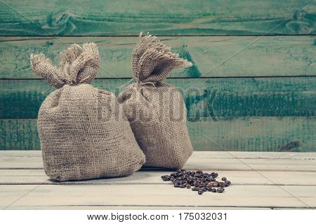 Coffee beans with burlap sacks over old wooden background