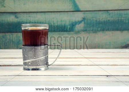 Cup of tea in vintage glass-holder on white wooden background