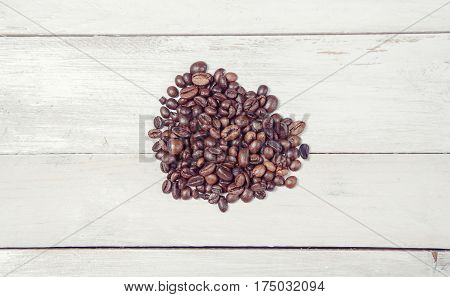 Heap of coffee beans on white wooden table