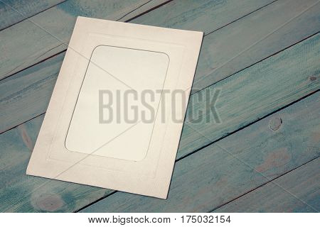 Retro white photo frame on wooden background. Top view
