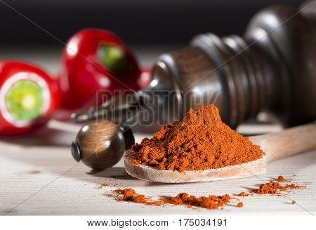 Ground pepper mill red pepper on a table with paprika and pepper mill