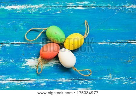 Colorful painted Easter eggs on twine on blue wood background template mockup flat lay closeup copy space for text