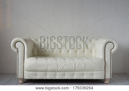 White leather sofa on white wooden floor near white textured wall