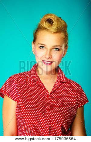 Fashion clothing disguise concept. Lovely young pin up girl in vintage hairstyle wearing retro red shirt. Studio shot on blue background