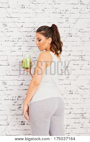 Young fit sportswoman drinking green healthy smoothie. Rear view of young curvy fit woman in gray leggings having a fresh vitamin juice. Brick wall background, mild retouch.