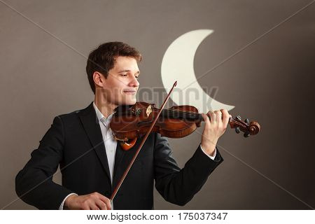 Music passion hobby concept. Young man man dressed elegantly playing on wooden violin. Studio shot on dark background with white moon