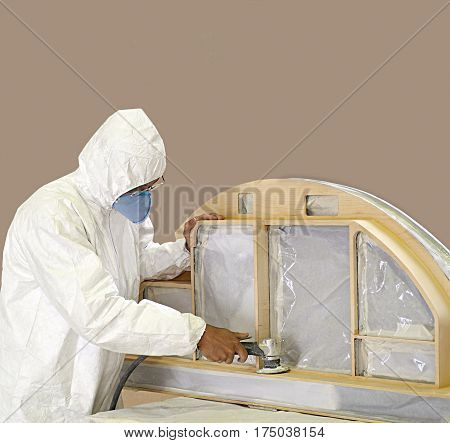 Studio shot of a joiner sanding a window on a neutral background