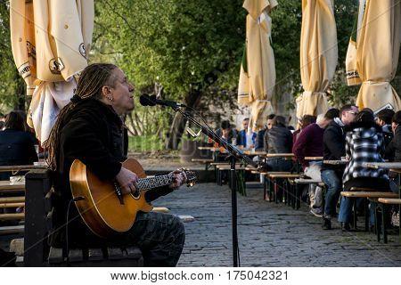 Czech Republic Prague 11.04.2014: A street musician play music near the river in a restaurant for guests