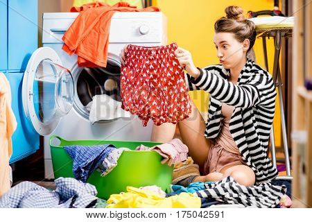 Young housewife holding pants sitting near the washing machine with colorful clothes at home