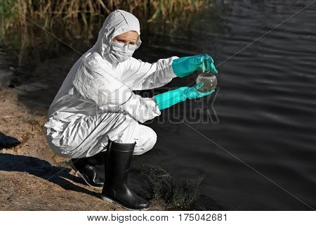 Oil spills concept. Woman with flask for expertise on shore