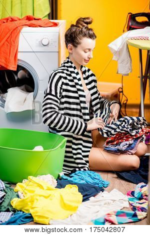 Young housewife putting together clothes sitting near the washing machine with colorful clothes at home