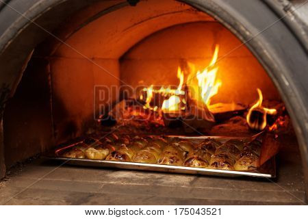 Apple halves being roasted in wood fired oven, professional kitchen of a restaurant