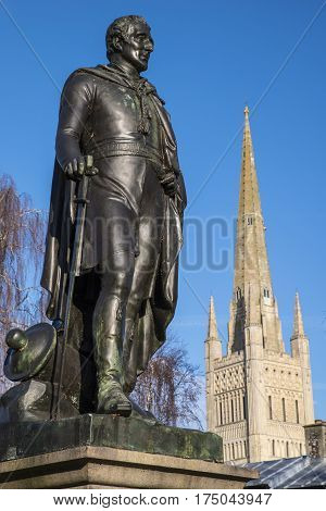 A statue of the Duke of Wellington with the beautiful Norwich Cathedral in the background in the historic city of Norwich UK.