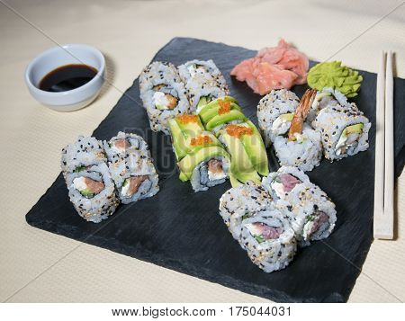 Close up of sushi served on black plate. Delicious japanese cuisine sushi prepared for one person. Fresh sushi served to eat