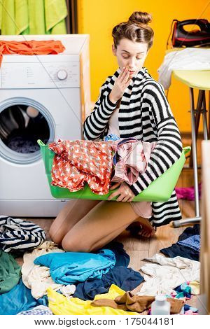 Young housewife holding a basket with clothes near the washing machine sitting on the floor at home