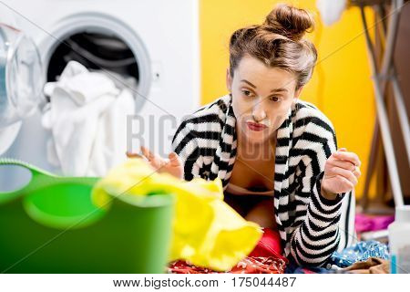 Tired housewife sitting on the floor near the washing machine with colorful clothes at home