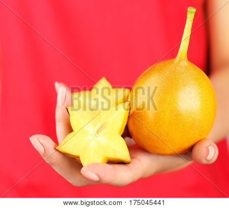 Woman holding starfruit and passionfruit