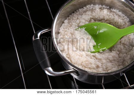 Spoon with rice in metal pan on hotplate