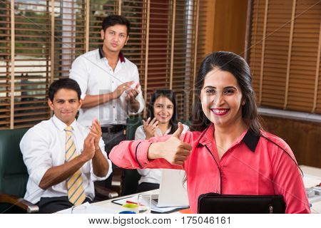 Young and beautiful indian female business executive laughing and sitting in front of her team with folder in hand, indian business woman in the office looking at camera