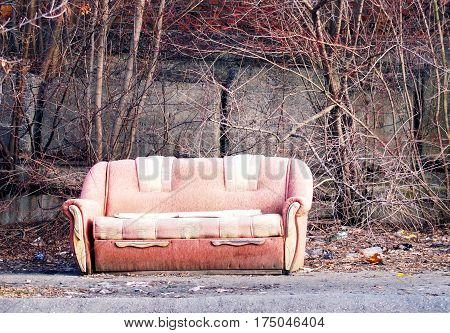 Lonely dirty abandoned sofa left in the street with junk