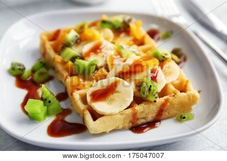 Delicious waffle with fruits and syrup on white plate