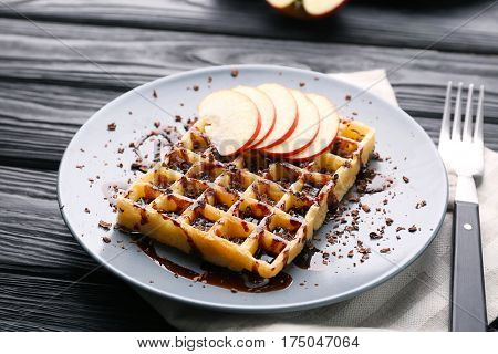Delicious waffle with apple slices, syrup and chocolate shavings on plate