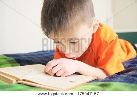 children education boy reading book lying on bed child portrait with book education concept interesting storybook