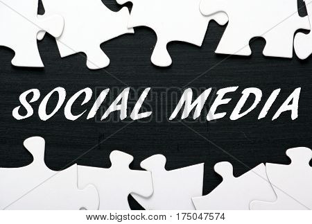 The words Social Media in white text on a blackboard with jigsaw puzzle pieces as a concept for unlocking content marketing