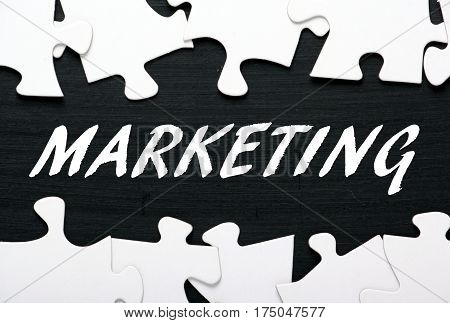 The word Marketing in white text on a blackboard between jigsaw puzzle pieces as a concept for unlocking advertising solutions
