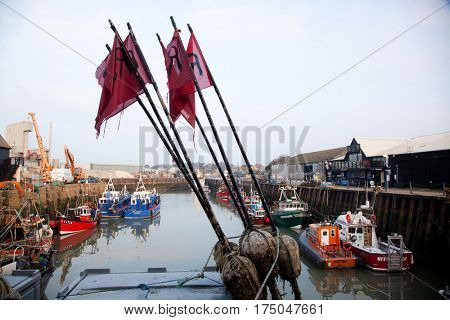 WHITSTABLE, UK -February 24, 2017: Fishing Boats in Whitstable Harbour in portrait view with warehouse in background