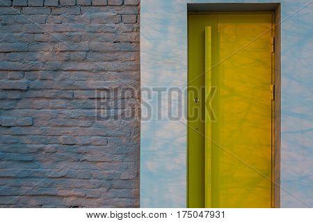 Gray brick wall with a design yellow door. Shadows drops on their surfaces. Outdoors. Closeup. Horizontal.