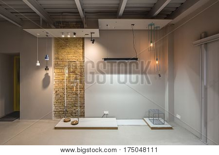 Interior in a loft style with gray walls and a narrow brick wall. There is a yellow door, many different glowing lamps, design metal stool. Horizontal.