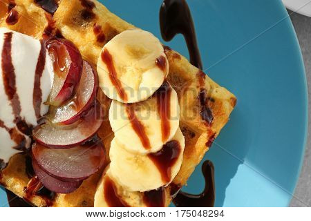 Tasty waffle with delicious fruits, ice-cream and syrup on blue plate, close up