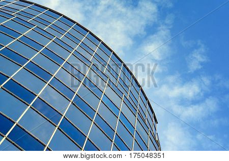 Curved glass facade of modern building against blue sky. Perspective view from below upwards. Abstract background