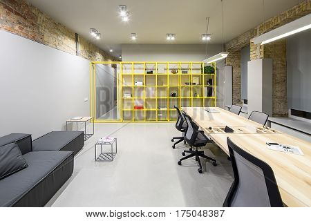 Loft style office with gray and brick walls. There are glowing lamps, dark sofa with pillow, wooden tables with chairs, small metal tables, metal yellow shelves with accessories, opened door.