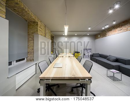 Empty office in a loft style with gray and brick walls. There are glowing lamps, wooden tables with chairs, metal yellow lockers, dark sofas with pillows, small metal table, window with curtain.