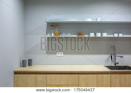 Wooden lockers with a tabletop with a sink in the kitchen in a loft style. Over the tabletop there are shelves with cups, glasses, bottles and plates. Two candles stand on the tabletop. Horizontal.