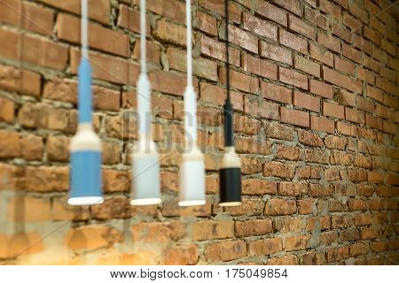 Low aperture photo of the glowing hanging multi-colored lamps in a loft style on the brick wall background. Closeup. Horizontal.