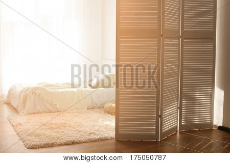Interior of beautiful room with folding screen and bed