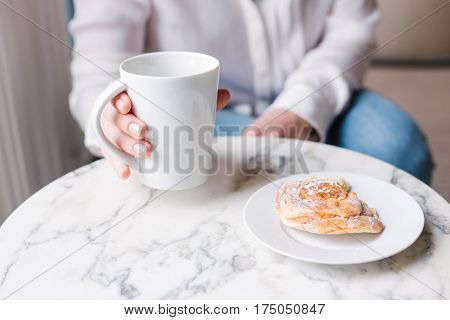 Closeup shot of a woman holding coffee mug. Close up of young woman's hand holding a cup of hot coffee. Relaxed girl eating breakfast on the marble table. Shallow depth of field with focus on coffee mug.