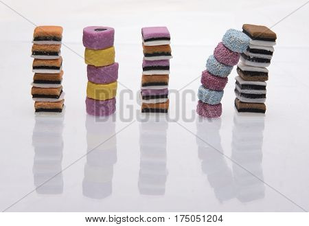 Separate stacks of licorice all-sorts on a white background