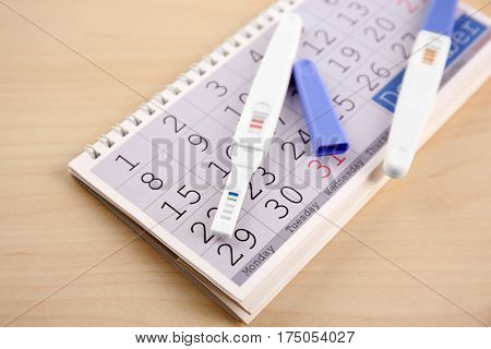 Pregnancy tests and calendar on wooden background