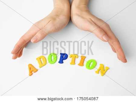 Female hands and word ADOPTION on white background