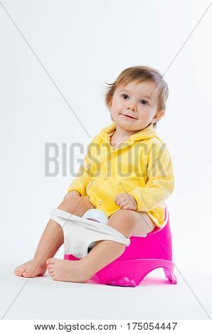 Little smiling girl sitting on a pot. Isolated on white background