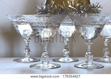 Ornate vintage stemware filled with champagne with a party hat resting on top