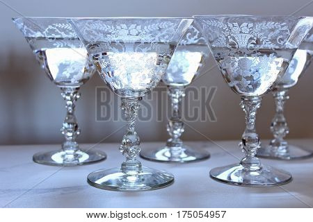 Elegant vintage etched glass cocktails filled with champagne on display.