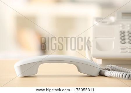 Telephone with picked up receiver on wooden table in office
