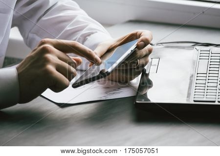 Business man drinking coffee and using laptop computer and mobile smart phone at home, young man browsing internet on phone, e commerce or online working from home, IOT internet of things concept.