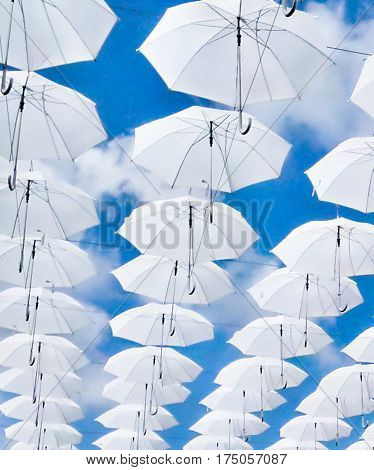 texture of white umbrellas on a blue sky background