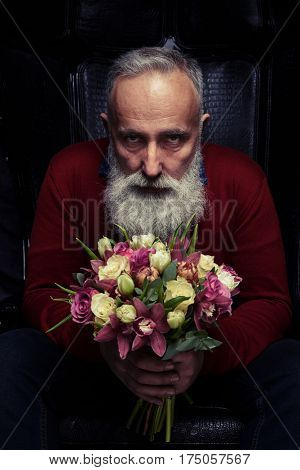 Close-up shot of bearded tough man sitting in an armchair. Holding a bouquet of tulips and roses isolated over black background